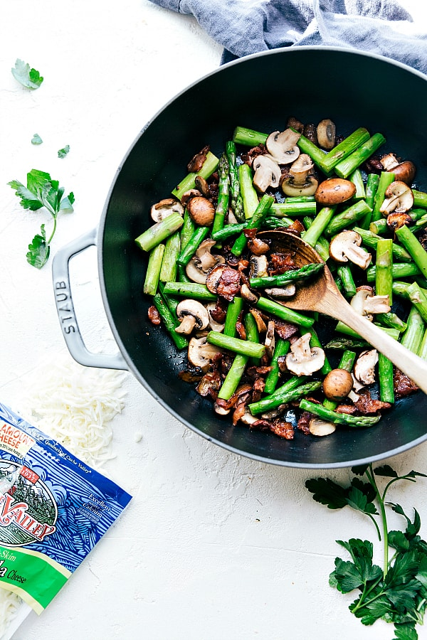 Cheesy Chicken, Asparagus, Bacon, and Mushroom Shells in a skillet being stirred with a wooden spoon.