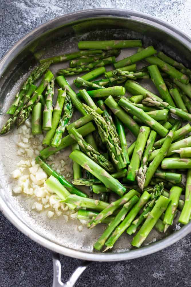 Asparagus cooking with onion in a saute pan.