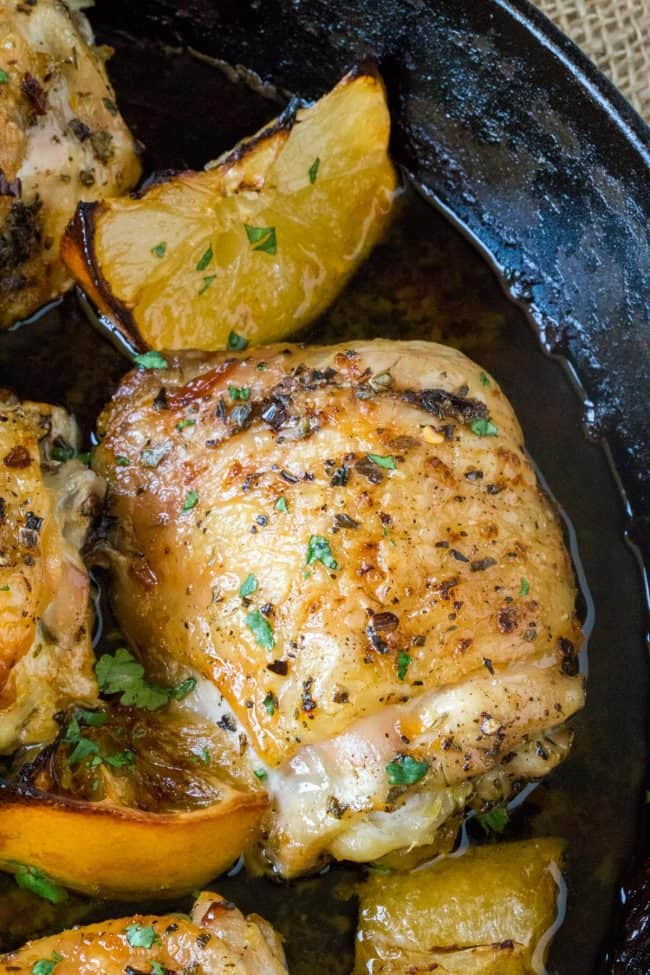 Easy Greek Lemon Chicken in a cast iron skillet along with roasted lemon wedges in an easy pan sauce.