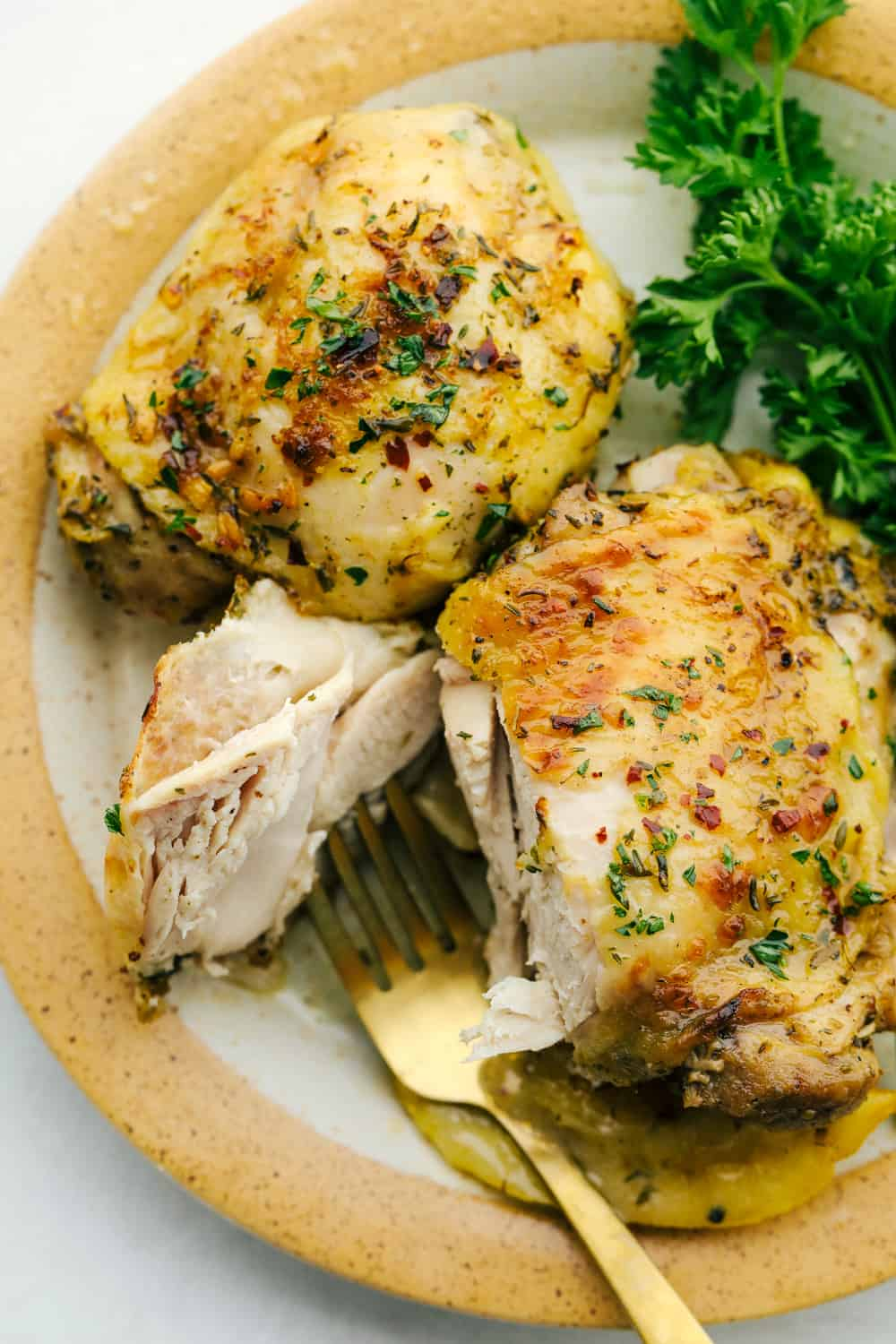 Greek Lemon chicken on a plate, and cut by a fork.