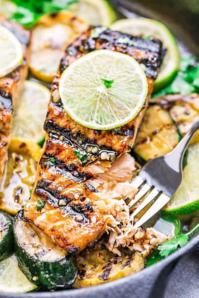Close-up of Honey Lime Salmon fillet over sliced zucchini and limes