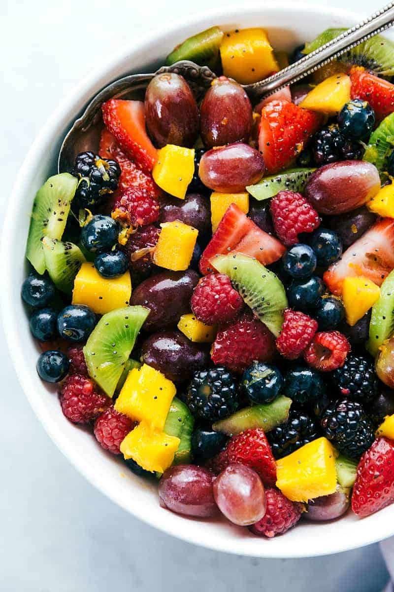 Blackberry-Lime Fruit Salad with tons of fresh fruit in a white bowl.