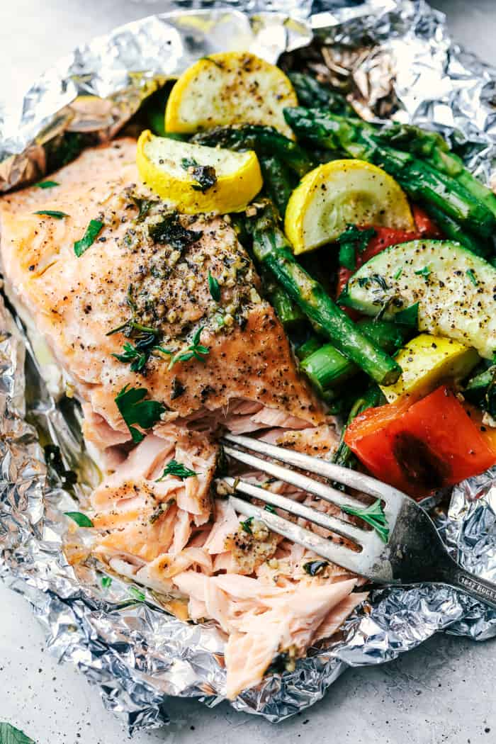 Butter Garlic Herb Salmon Foil Packets with a fork pulling the salmon apart.