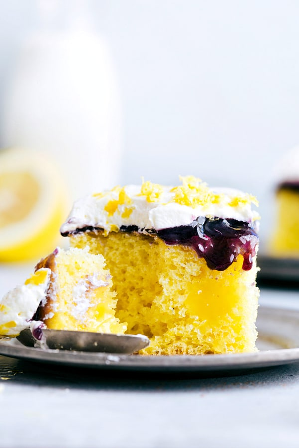 Slice of Lemon Blueberry Poke Cake on a plate.