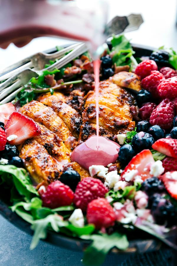 Grilled Berry Feta Chicken Salad with dressing being poured over it.
