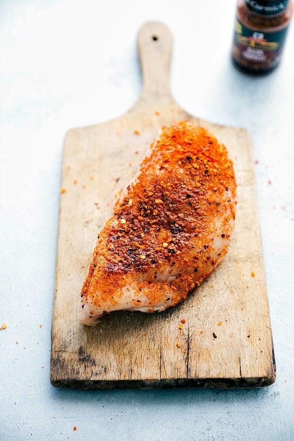 Seasoned chicken on a wooden plank.