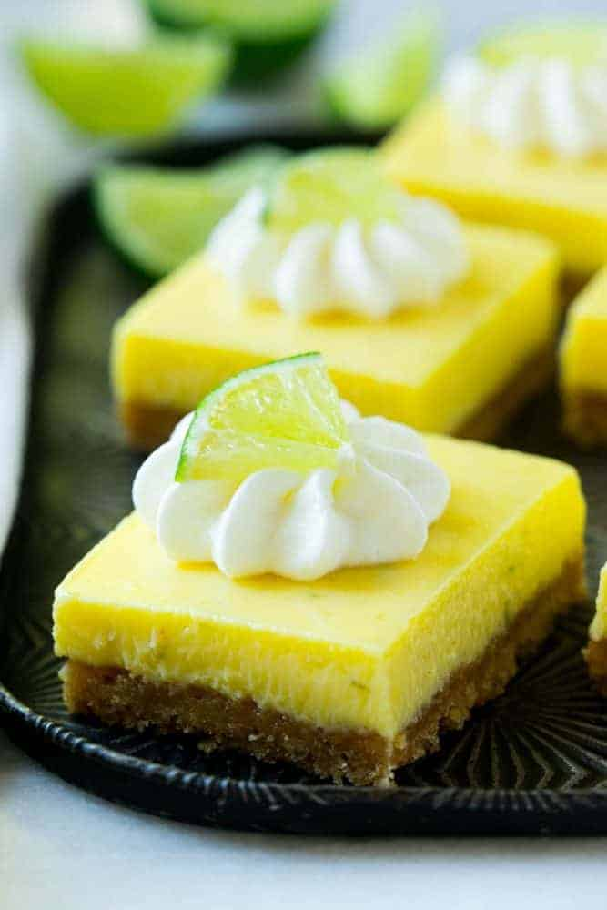 Key lime pie bars on a black plate.