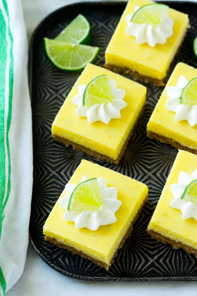 Areal view of finished key lime pie bars on a black plate.