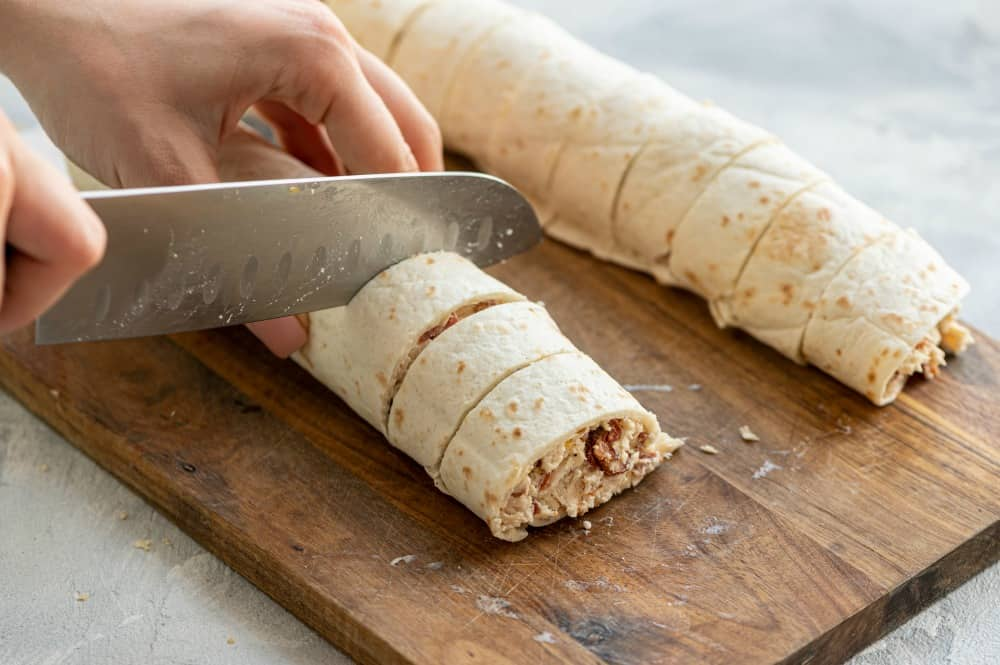 Cutting pieces of a chicken bacon ranch wrap.