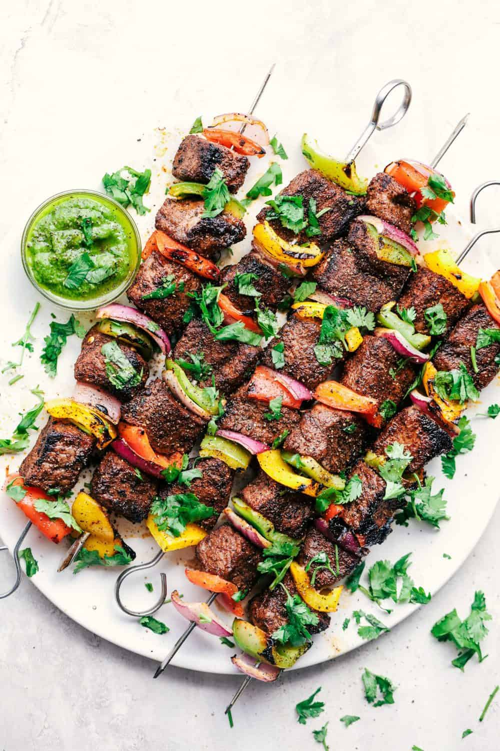 Finished Grilled Steak Fajita Skewers with Avocado Chimichurri on a plate.