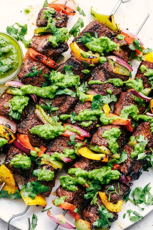 Grilled Steak Fajita Skewers with Avocado Chimichurri laid in a row.