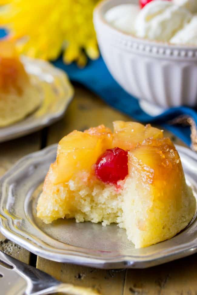 Easy, from-scratch, pineapple upside-down cupcake with a bite out to show the inside of this moist cake.