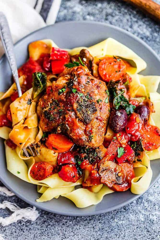 Slow Cooker Chicken Cacciatore over noodles on a gray plate.