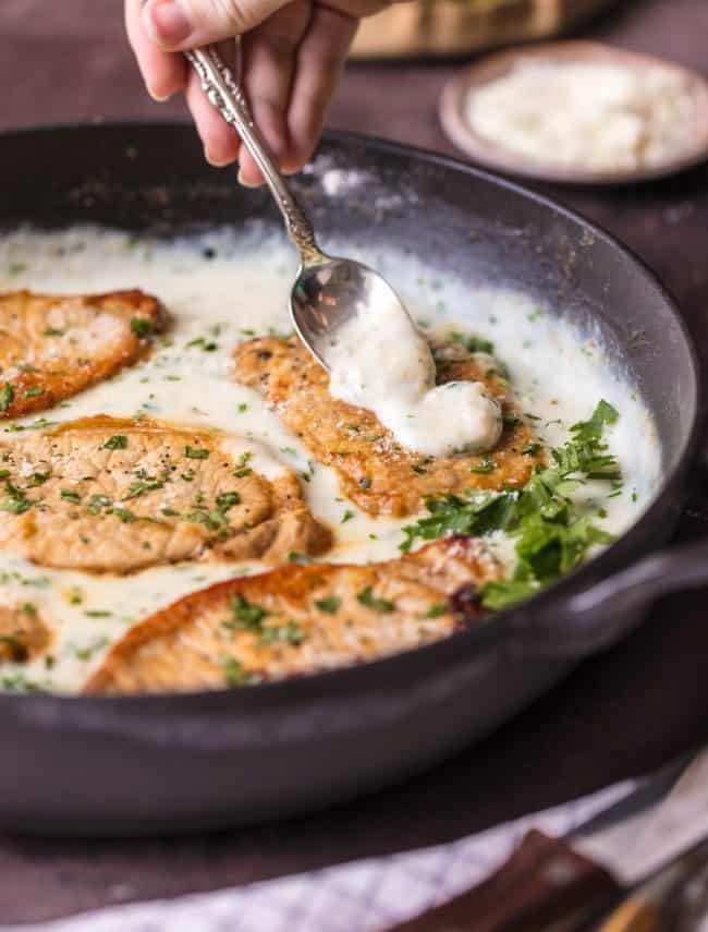 These Creamy Parmesan Pork Chops with a spoon pouring sauce over the pork chops in a skillet.