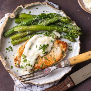 These Creamy Parmesan Pork Chops are sure to be a hit around the family table. The simple garlic parmesan sauce is oh so delicious and so easy anyone can make it in minutes.
