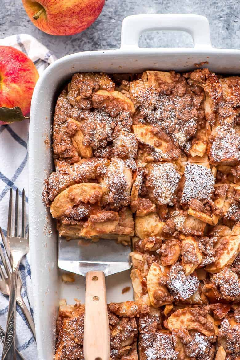 Overnight Cinnamon Apple French Toast Casserole being scooped out of a white baking dish with a spatula.