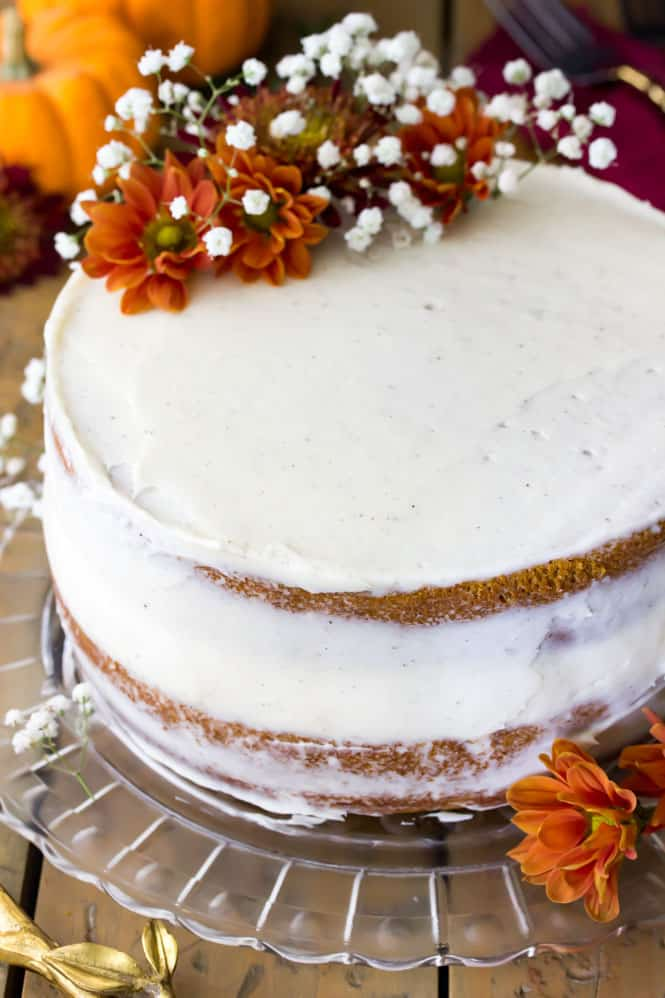 A soft, moist, and EASY Pumpkin Cake, iced and decorated with flowers.