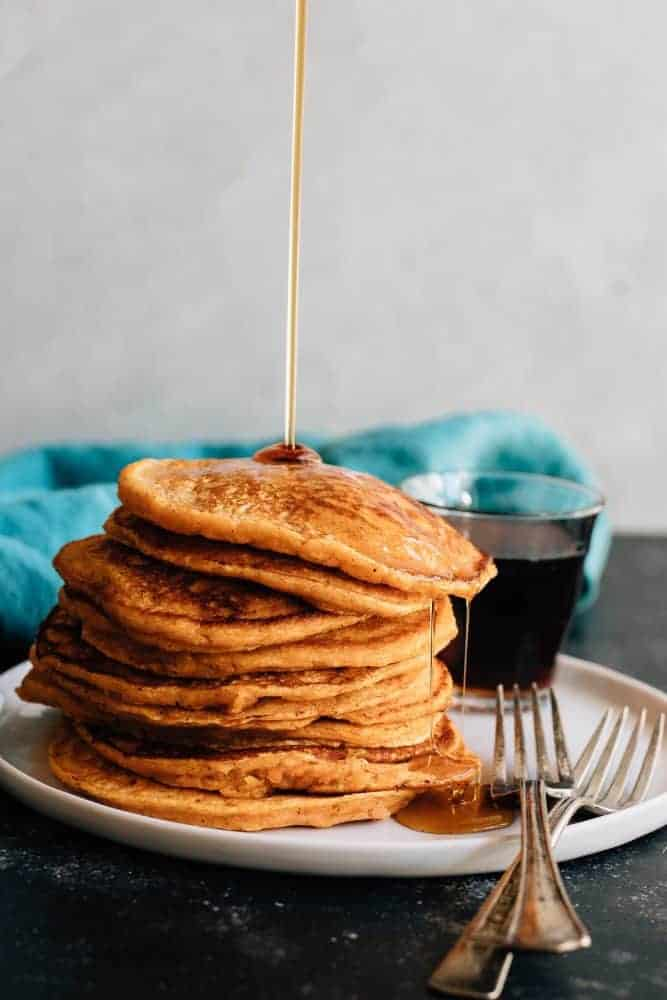 Maple Sweet Potato Pancakes stacked on a white plate.