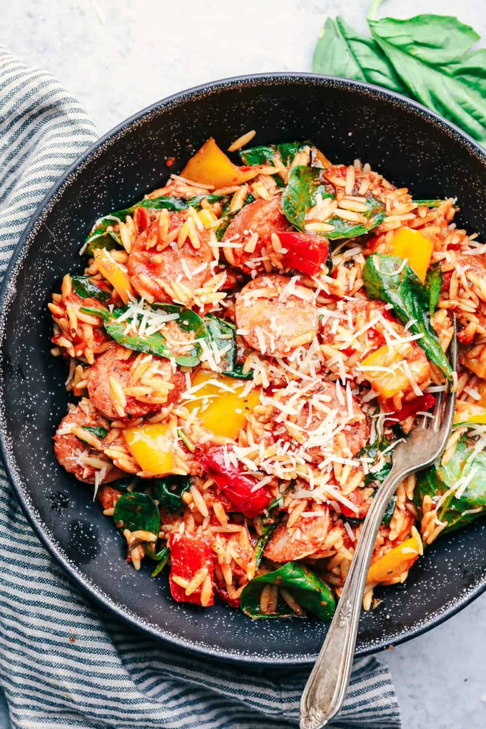 Italian Sausage and Vegetable Orzo Skillet on a black plate.