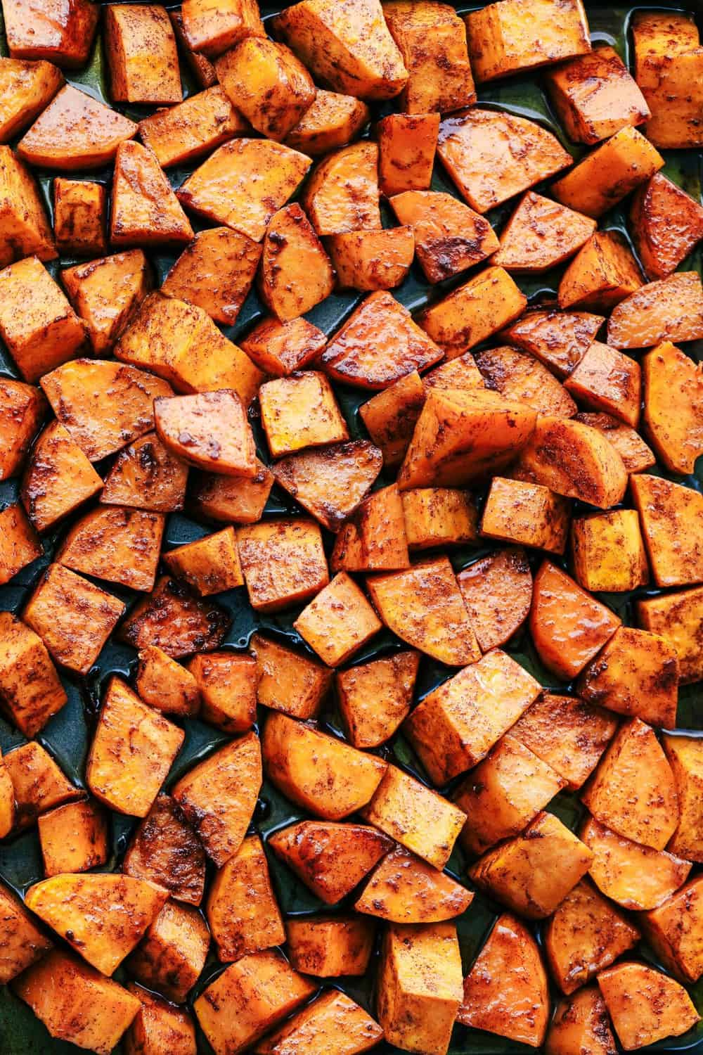 Roasted Honey Cinnamon Butter Sweet Potatoes spread out on a pan.