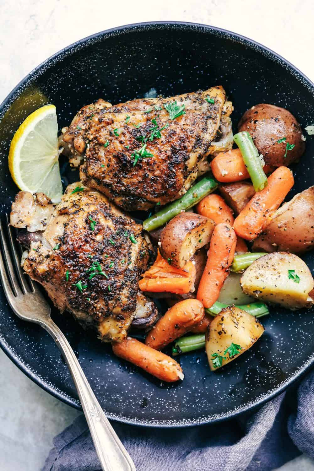 Slow Cooker Lemon Garlic Chicken Thighs and Veggies on a black plate.