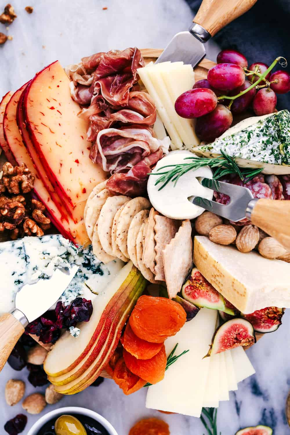 Cheese Board filled with meats, cheeses, nuts, and fruit.