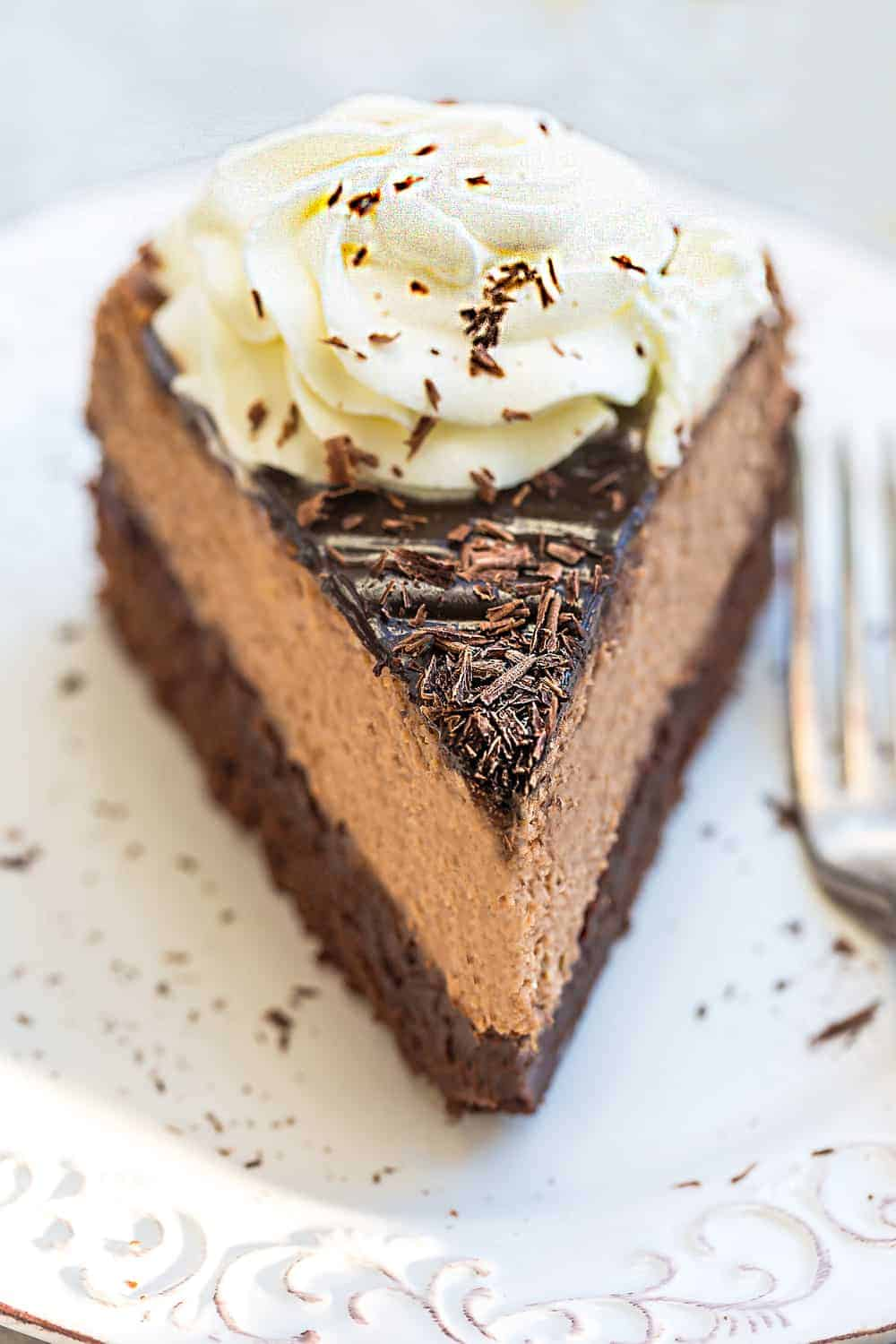Slice of Chocolate Brownie Cheesecake on a white plate.