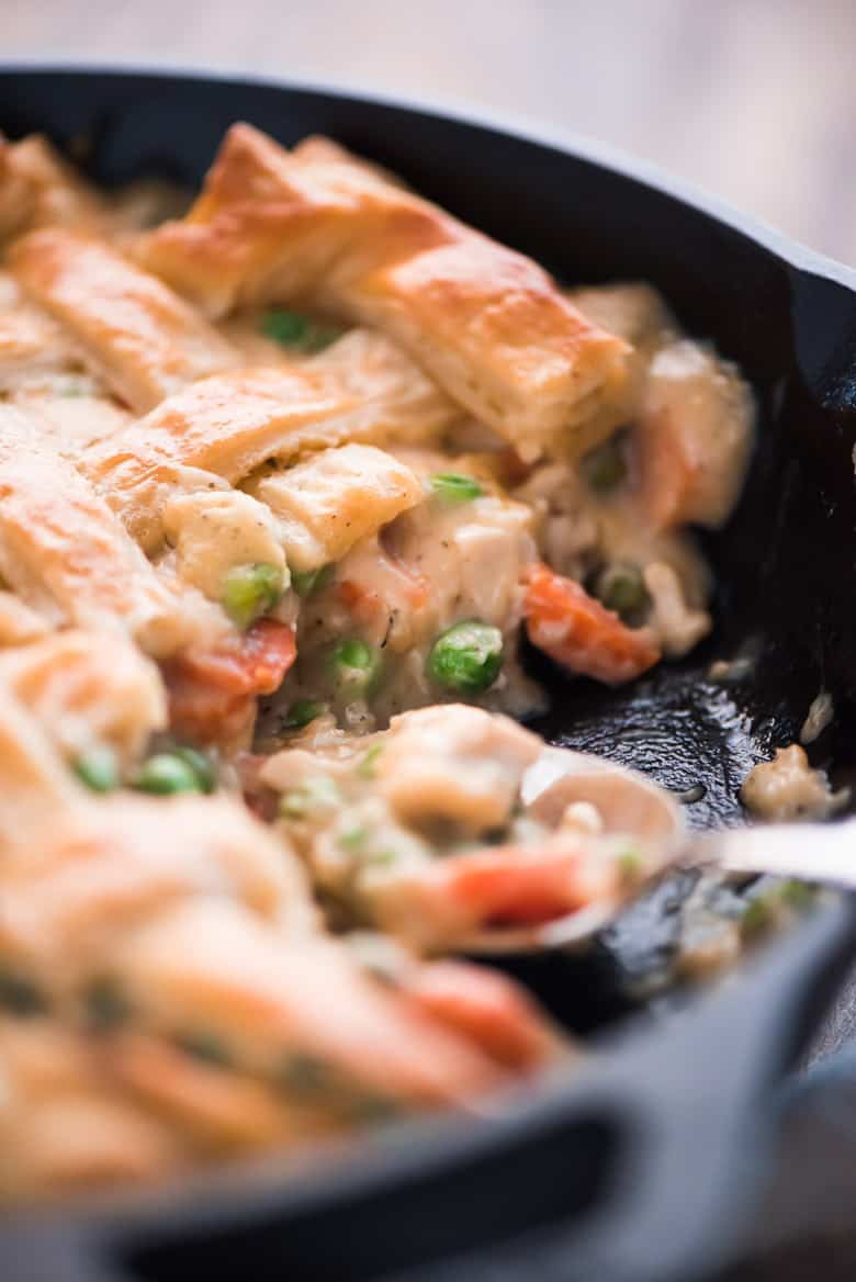 One Skillet Chicken Pot Pie being scooped out of a skillet with a spoon.