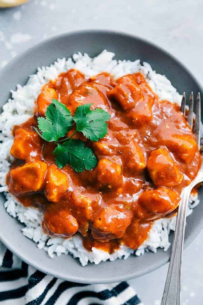 Easy Butter Chicken over white rice in a grey bowl with a fork.