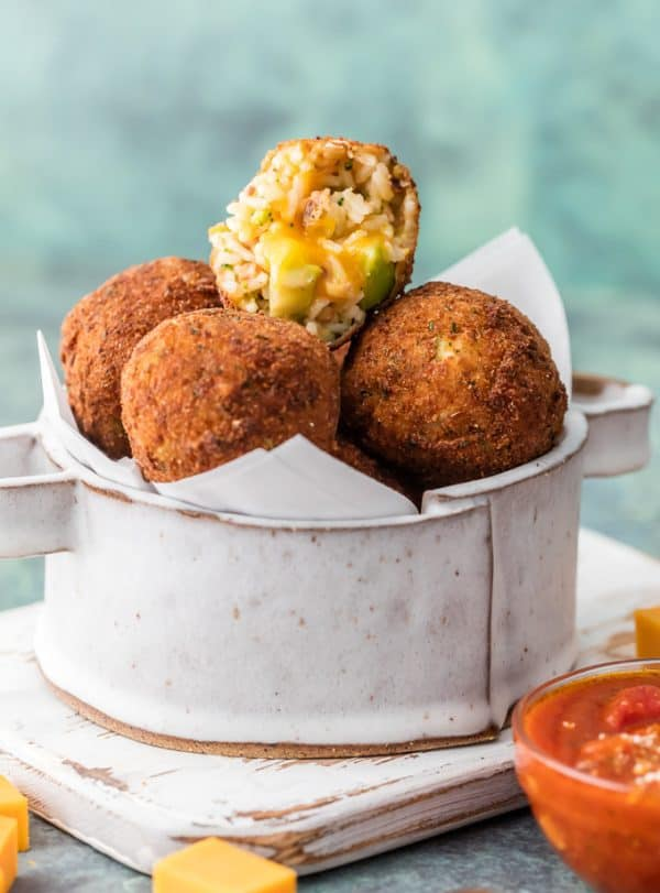 One Bacon Broccoli Cheese Arancini cut in half and stacked on others.
