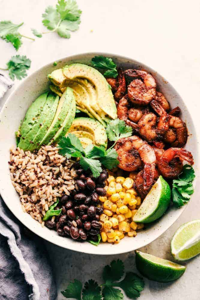 Blackened Shrimp Avocado Burrito Bowl in a white bowl with limes and cilantro on the side.
