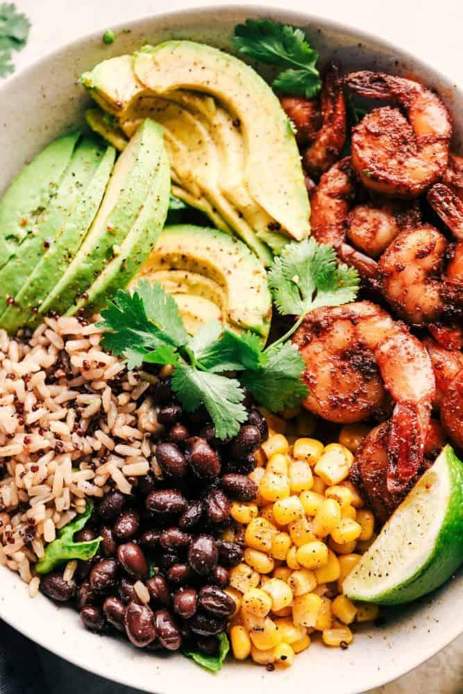 Blackened Shrimp Avocado Burrito Bowl with rice in a white bowl.