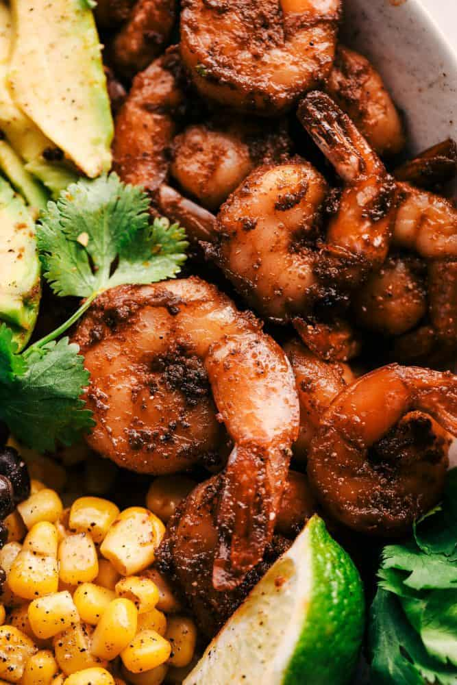 Blackened Shrimp Avocado Burrito with cilantro and lime for garnish.