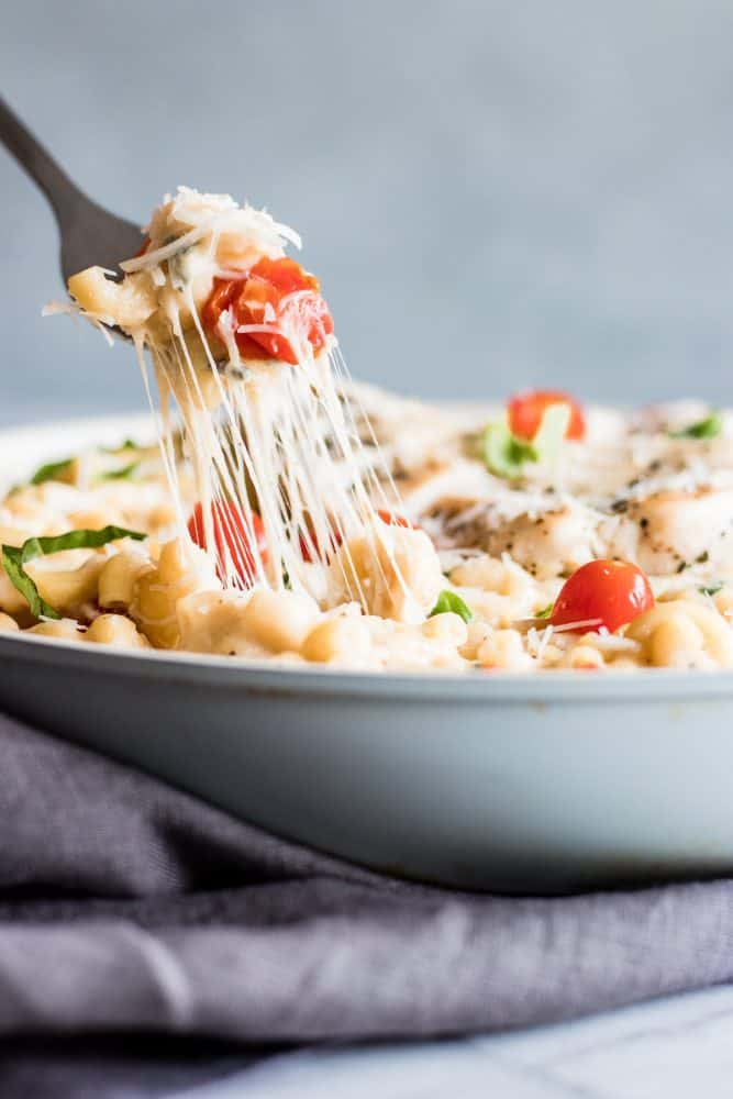 Chicken Caprese Macaroni and Cheese in a white bowl with a fork.