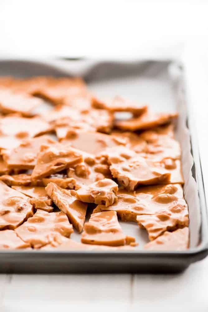 peanut brittle in a sheet pan laying on top of parchment paper.