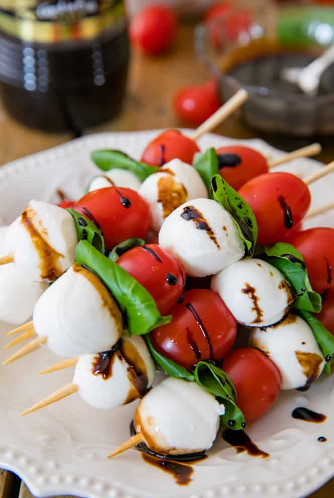 Caprese Skewers on a white plate with balsamic vinegar drizzled on top.