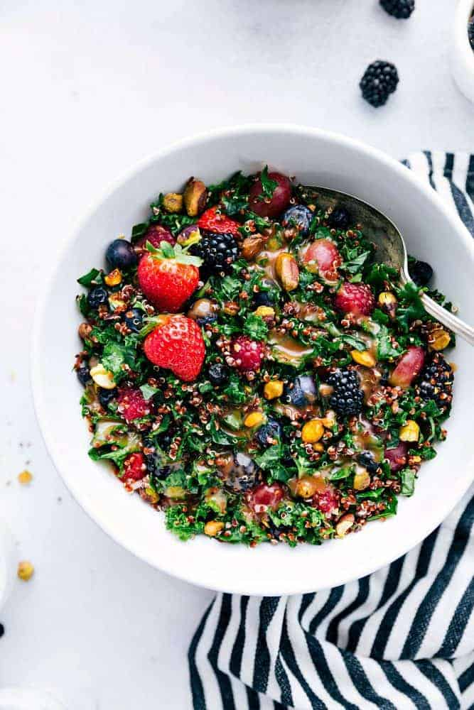 Berry, quinoa, and kale salad in a white bowl with a metal spoon on a black and white striped cloth