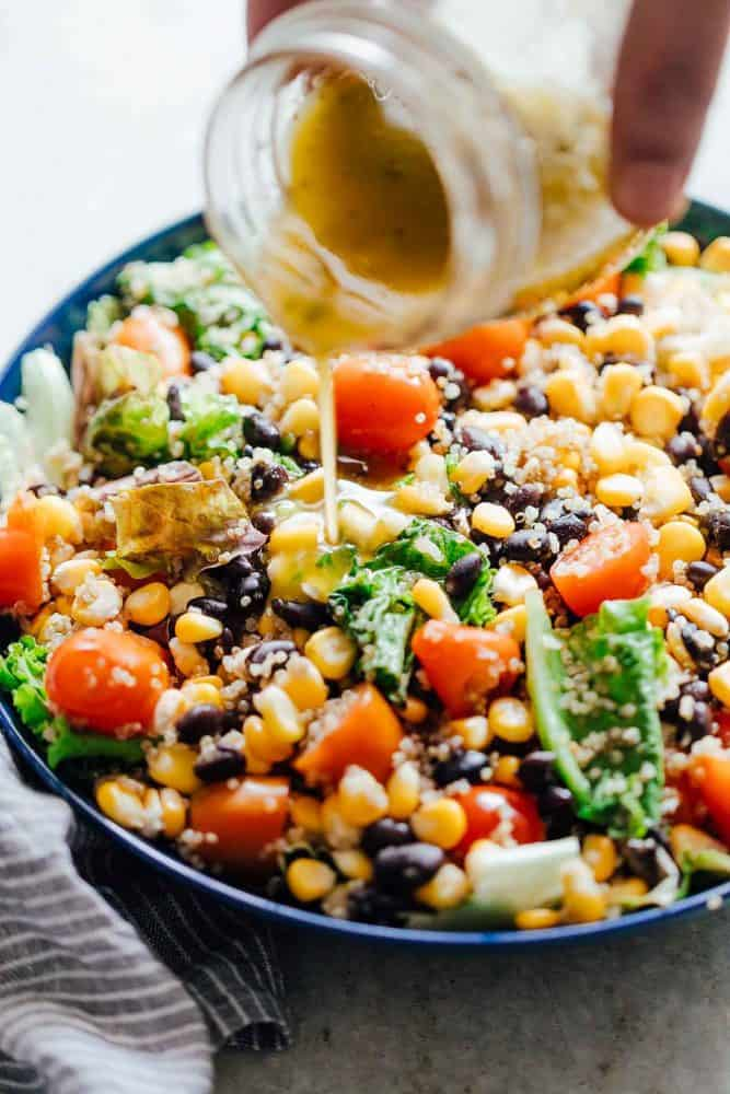 Pouring dressing on southwest quinoa bean salad.