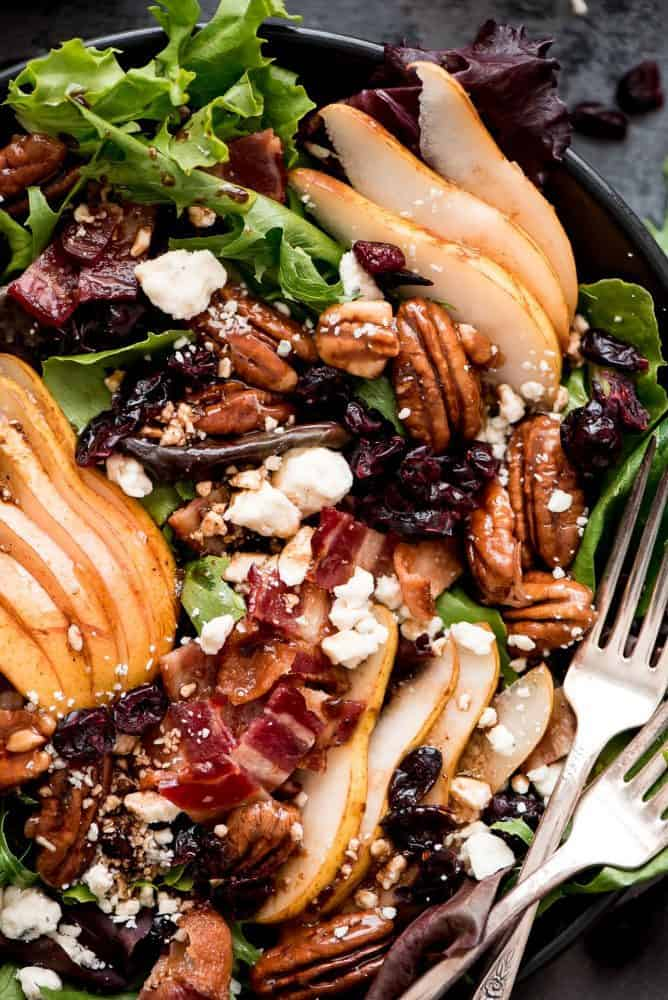 Bacon Pear Gorgonzola Salad in a black bowl with two forks.