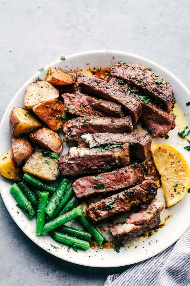 Marinated and cooked steak with cooked potatoes, green beans and sliced lemons on a white plate.