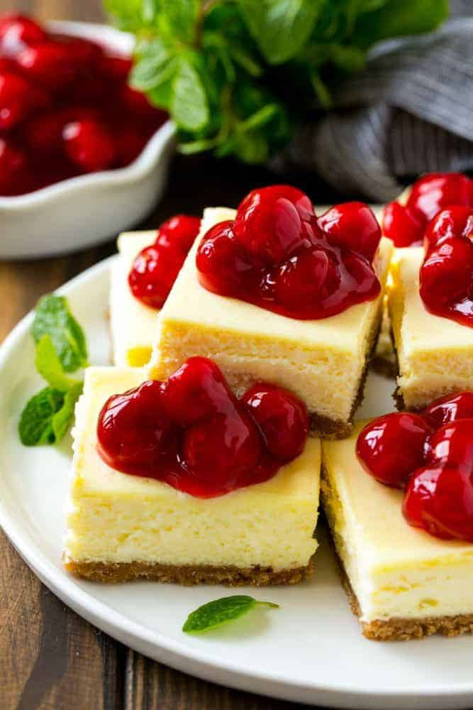 These cherry cheesecake bars on a white plate with cherries on top.