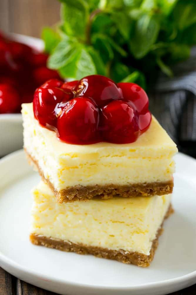 Closeup of cherry cheesecake bars on a white plate with cherries on top.