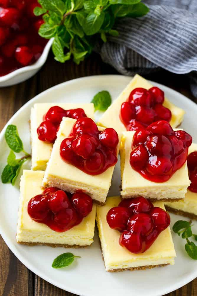 Cherry cheesecake bars on a white plate with cherries on top.