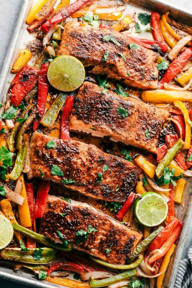Cooked Sheet Pan Garlic Lime Salmon with sliced lime and sliced sweet peppers.