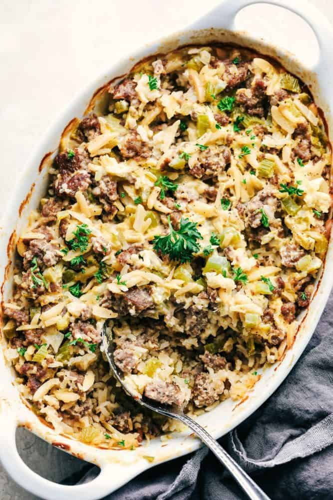 Easy Sausage and Rice Casserole in a white dish with a metal spoon.