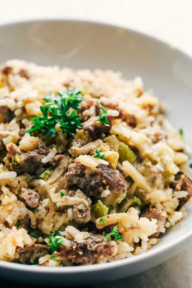 Easy Sausage and Rice Casserole in a white bowl with garnish on top.