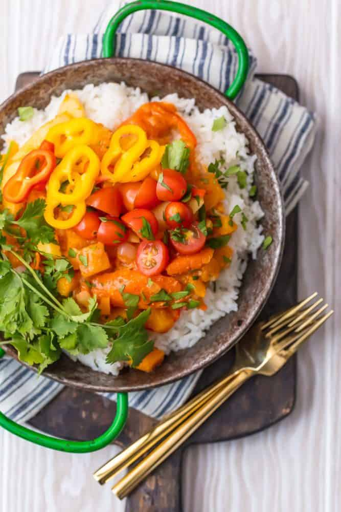 Vegetable Curry over white rice in bowl with forks on a cutting board.