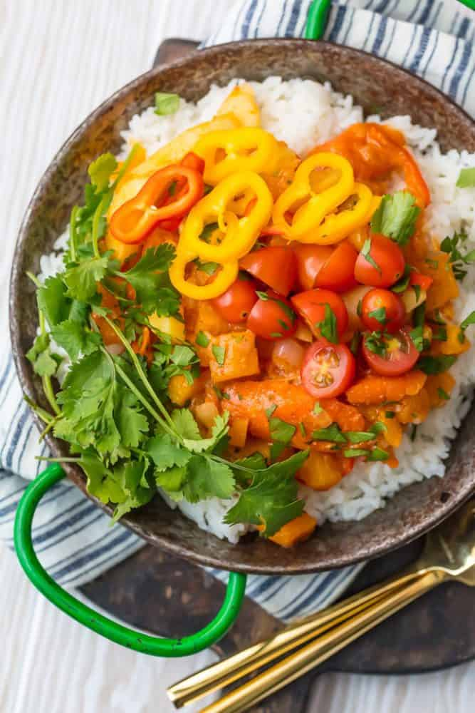 Vegetable Curry over white rice in a bowl with forks on a cutting board.
