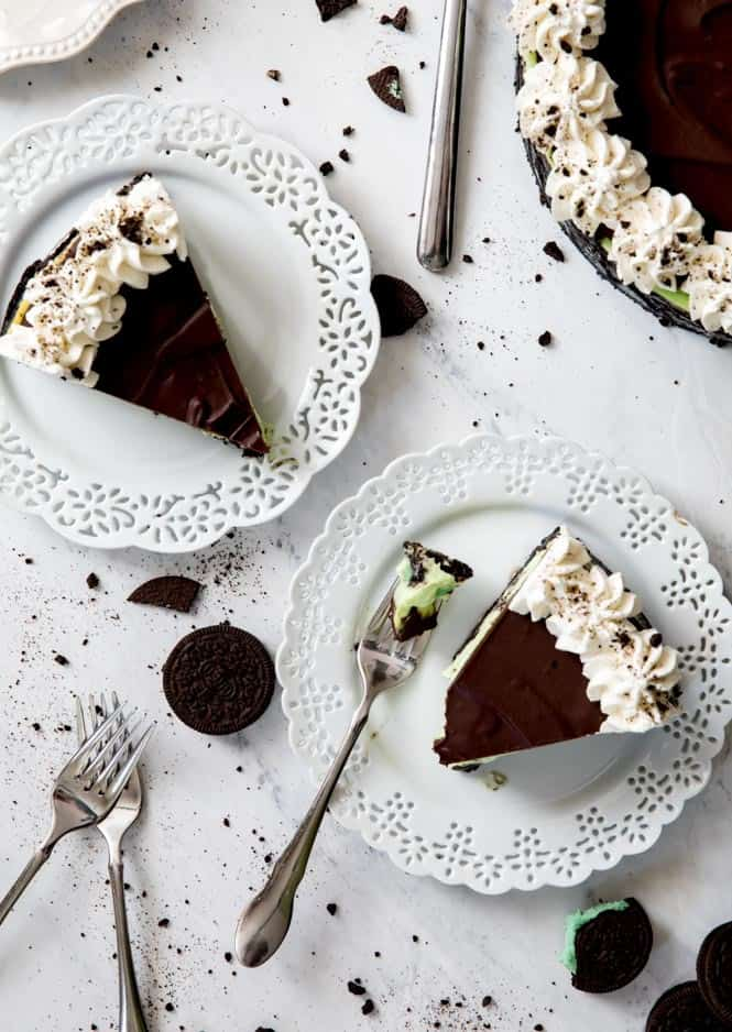 Two slices of Mint Oreo Cheesecake on white plates with metal forks.  There are also mint Oreos on the side.