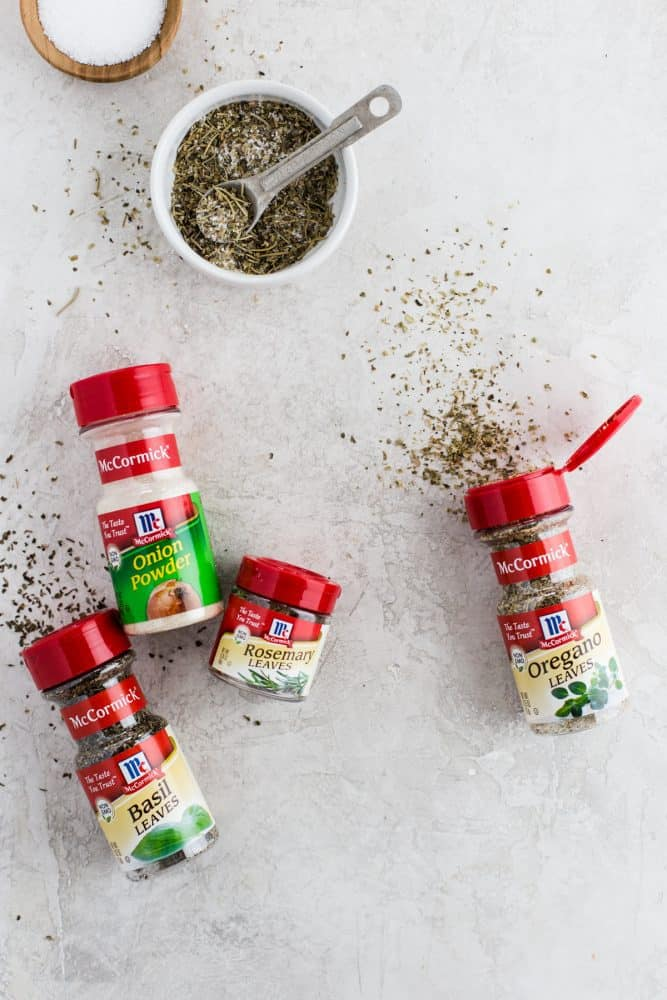 McCormick seasonings on a white table and a small dish of mixed seasonings.